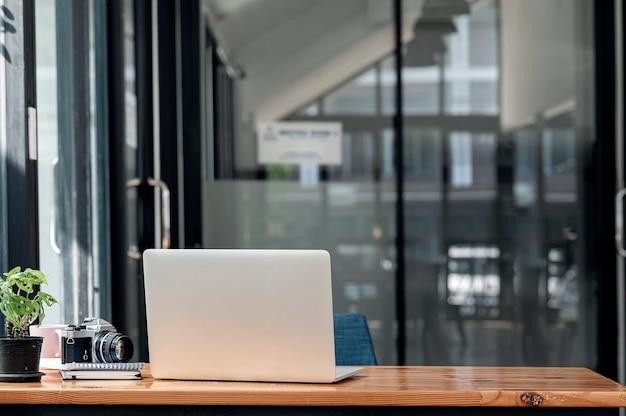 Vista posteriore del computer portatile sul tavolo di legno nella moderna stanza dell'ufficio con spazio per le copie.