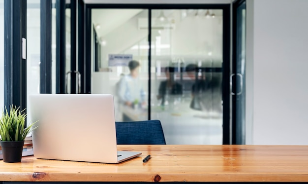 Vista posteriore del computer portatile su un tavolo di legno con sfocatura dello sfondo della gente di affari in una stanza moderna.