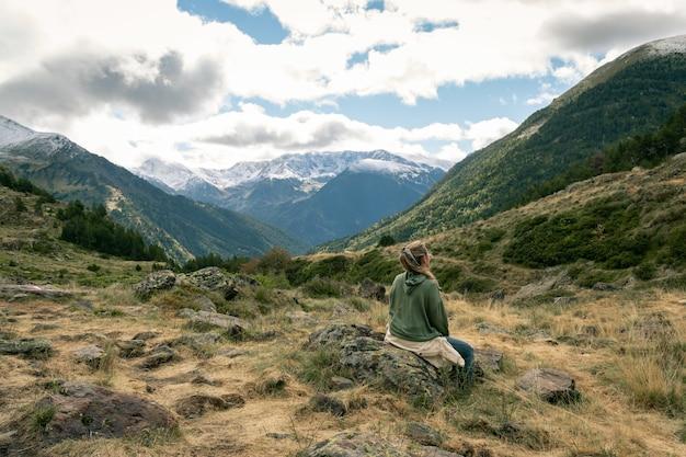Vista posteriore di una donna latina seduta su una roccia ricoperta di muschio nella valle zillertal, austria.