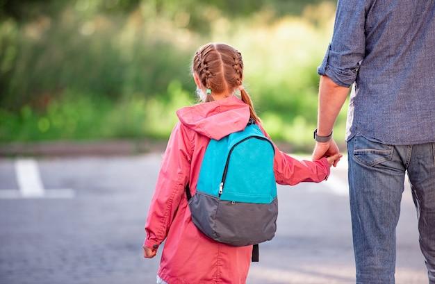 Vista posteriore della bambina con lo zaino che tiene la mano del padre