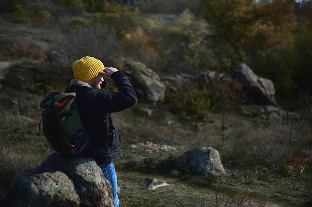 Vista posteriore di un uomo con lo zaino in spalla in cappello giallo con uno zaino seduto su una roccia e guardando in lontananza con la mano sopra la testa.