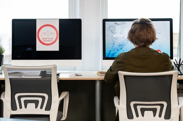Vista posteriore dell'operatore maschio del call center seduto davanti al monitor del computer accanto a uno con l'annuncio di mantenere la distanza