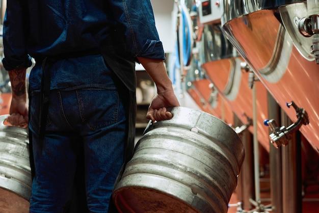 Vista posteriore del lavoratore maschio del moderno impianto di produzione di birra in abiti da lavoro che trasportano due cisterne mentre si muove lungo la fila di enormi serbatoi di acciaio