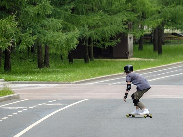 Vista posteriore di un uomo in uniforme nera che si muove ad alta velocità su uno skateboard