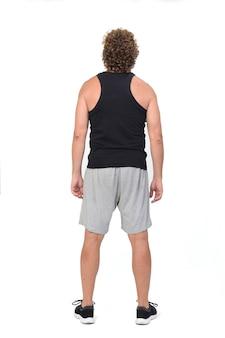 Vista posteriore di un uomo che indossa canottiere e pantaloncini sportivi su sfondo bianco