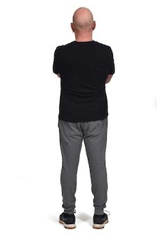 Vista posteriore di un uomo con abbigliamento sportivo su sfondo bianco, braccia incrociate