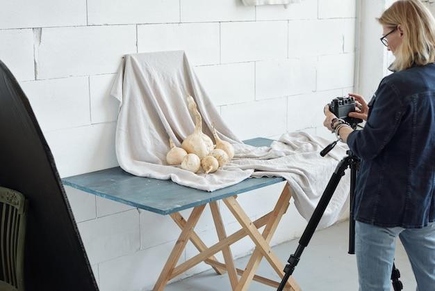 Vista posteriore della signora matura in giacca di jeans fotografare verdura su tessuto in studio fotografico