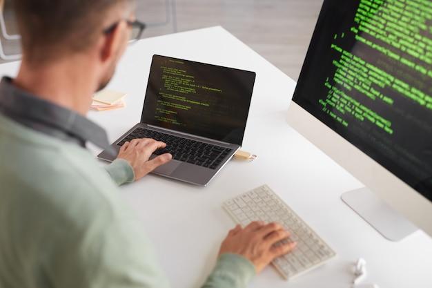 Vista posteriore del programmatore maturo seduto al tavolo in via di sviluppo programma su un computer desktop