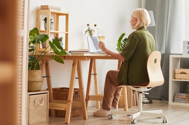 Vista posteriore della donna matura che beve vino e parla online con i suoi amici utilizzando laptop mentre è seduto al tavolo a casa