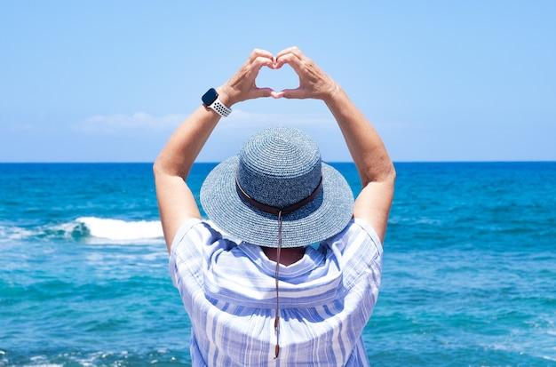 Vista posteriore di una donna matura con cappello blu che guarda l'orizzonte sull'acqua facendo a forma di cuore con le mani. concetto di amore e libertà