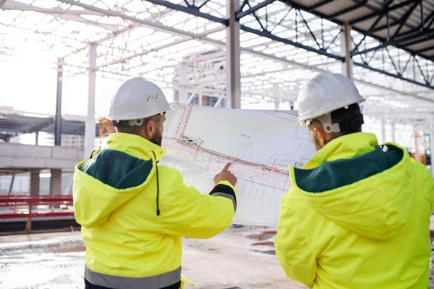 Vista posteriore di ingegneri uomini in piedi all'aperto in cantiere, tenendo progetti.