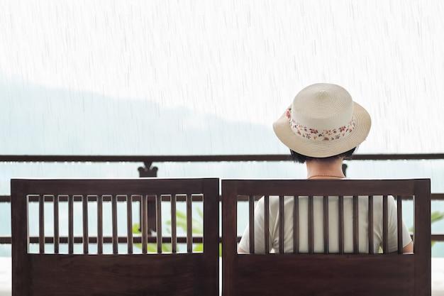 Vista posteriore della donna di mezza età sul banco in una giornata piovosa