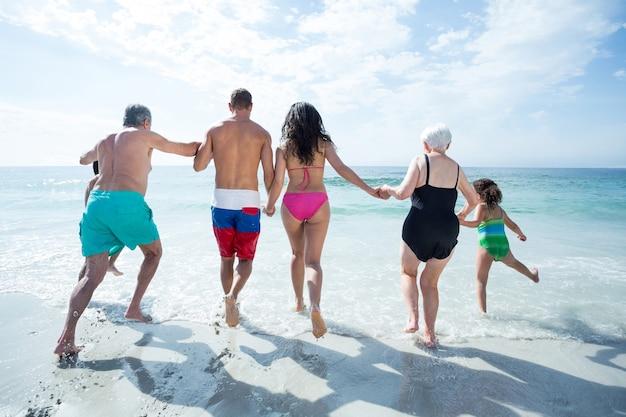 Vista posteriore della famiglia multi-generazione in spiaggia