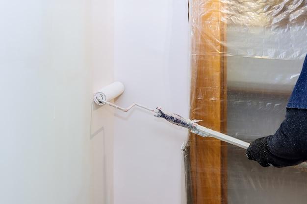 La vista posteriore del pittore dipinge il muro con un rullo nella stanza