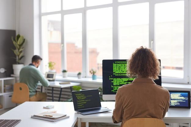 Vista posteriore di persone che lavorano con il nuovo software sui computer al tavolo in ufficio