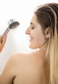 Ritratto di retrovisione di donna sexy che si lava sotto la doccia
