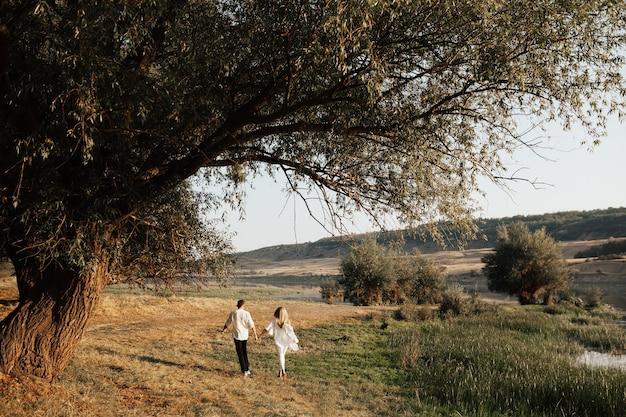 Vista posteriore di una coppia romantica mano nella mano e camminare attraverso il parco estivo.