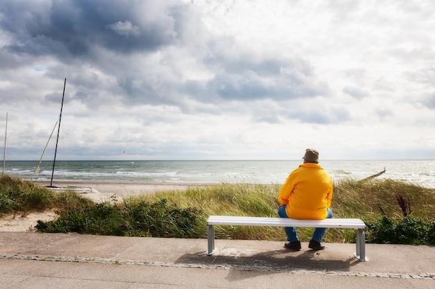 Vista posteriore dell'uomo anziano seduto sulla panchina bianca, rilassante sulla spiaggia. sfondo di vacanza. costa del mar baltico, destinazione di viaggio