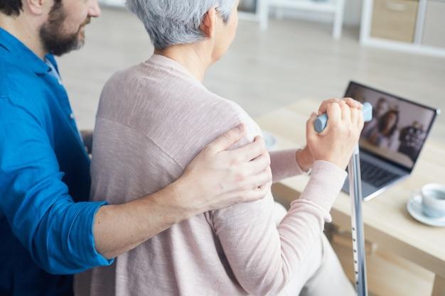 Vista posteriore della donna senior con badante a parlare con la sua famiglia online sul computer portatile