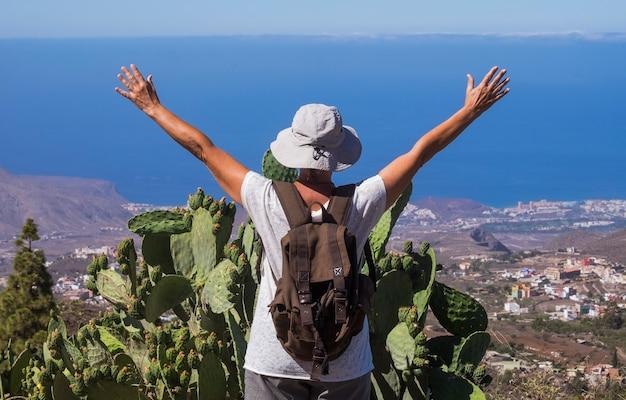 Vista posteriore della donna anziana con le braccia alzate che viaggiano nel paesaggio montano di tenerife, orizzonte sul mare - anziani in pensione attivi e concetto divertente