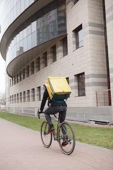 Vista posteriore del colpo di un corriere che indossa uno zaino termico, in bicicletta in città