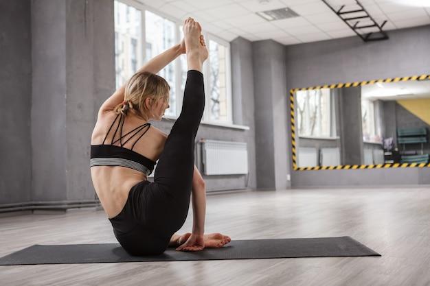 Colpo di vista posteriore di una donna flessibile che fa esercizio di yoga di stretching in palestra studio