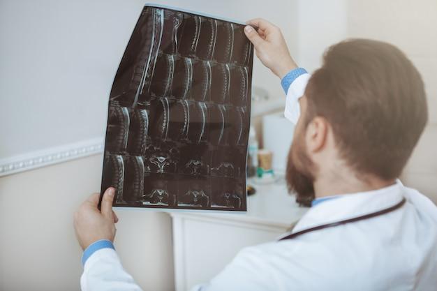 Colpo di retrovisione di medico maschio irriconoscibile che esamina le scansioni di mri di un paziente