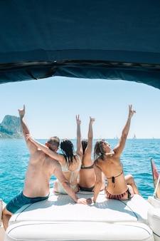 Vista posteriore di un piccolo gruppo di amici in bikini seduti sulla barca e ammirando la vista del mare fotografie stock