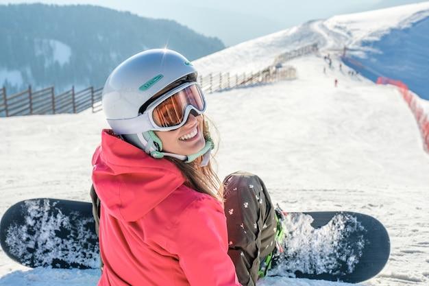 Vista posteriore dello snowboarder in abbigliamento sportivo con attrezzatura che riposa in cima alla pista da sci che gode della vista