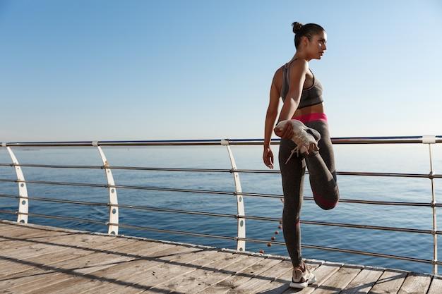 Vista posteriore della sportiva che allunga la gamba prima di correre lungo il mare.
