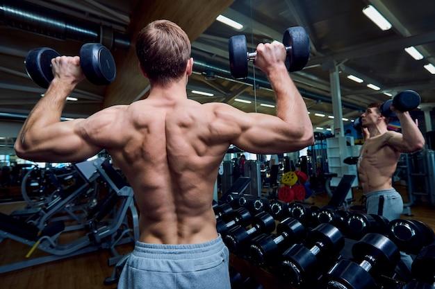 Vista posteriore di un uomo sportivo con manubri in braccio in palestra.