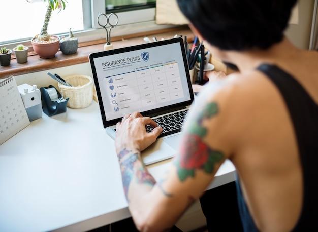 Retrovisione dell'uomo tatuato che controlla sul modulo di assicurazione