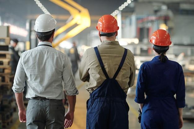 Vista posteriore di tre professionisti contemporanei in caschi e indumenti da lavoro in piedi nel corridoio all'interno dell'officina dell'impianto industriale