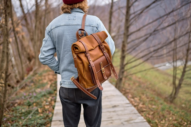 Uomo del viaggiatore di retrovisione che esplora i paesaggi della natura in primavera, camminando attraverso da solo