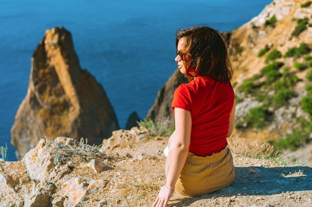 Vista posteriore della donna del viaggiatore in piedi sul bordo della scogliera davanti al fantastico paesaggio marino, concetto di viaggio.