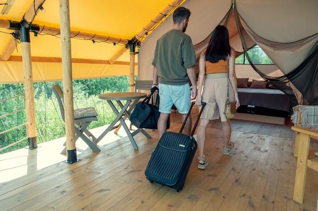 Vista posteriore di una coppia in viaggio con bagagli che entra nella camera da letto della casa glamping