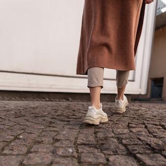 Vista posteriore sulla giovane donna alla moda in cappotto lungo alla moda in pantaloni beige in scarpe da ginnastica alla moda in pelle ragazza alla moda in abiti casual primaverili cammina lungo la strada di pietra in città. stile casual. avvicinamento.