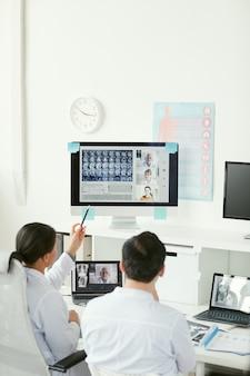 Vista posteriore di due medici seduti al tavolo ed esaminando le immagini radiografiche sul computer insieme ai loro colleghi