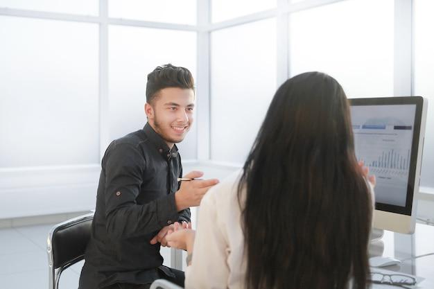 Retrovisore. due dipendenti discutono di questioni di lavoro seduti alla scrivania in ufficio