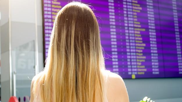Vista posteriore del turista femminile alla ricerca sulla scheda di pianificazione delle informazioni in aeroporto.