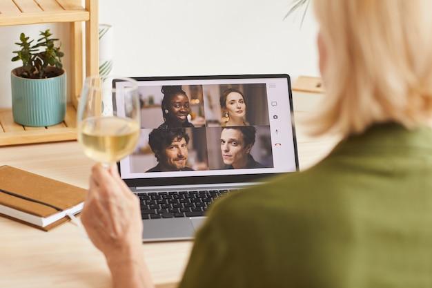 Vista posteriore della donna che beve vino e parla online con i suoi amici utilizzando il suo laptop a casa