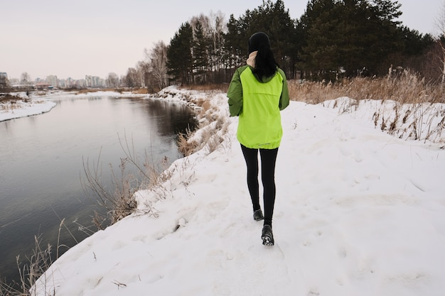 Vista posteriore della donna in giacca verde che corre lungo la riva invernale con erba secca lunga