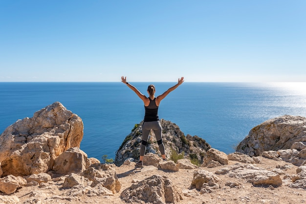 Vista posteriore di una donna che si diverte durante una gita in montagna, in piedi sul ciglio della montagna, godendosi la sua vista, a braccia aperte, in una giornata di sole []