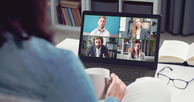 Vista posteriore della donna che tiene tazza stare a casa facendo videochiamata online utilizzando laptop, comunicazione a distanza