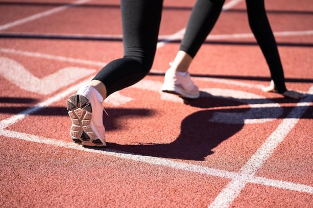 Vista posteriore del pareggiatore donna sulla pista da corsa sempre pronto per iniziare a correre