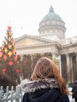 Vista posteriore della donna guarda l'albero di natale vicino alla cattedrale di kazan a san pietroburgo