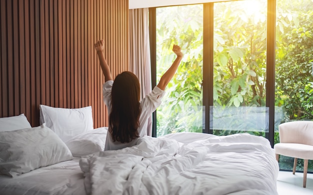 La retrovisione di una donna fa l'allungamento dopo essersi svegliato di mattina, guardando una bella vista della natura fuori dalla finestra della camera da letto
