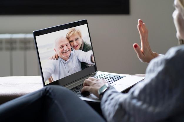 Retrovisione di una donna che parla su una videochiamata di famiglia con i suoi genitori da casa