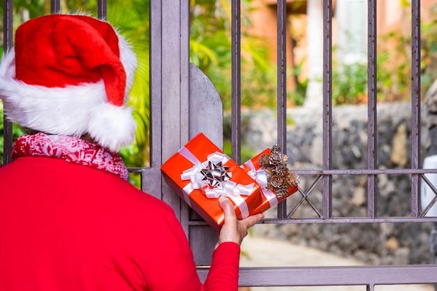 Vista posteriore di una donna che indossa un cappello di babbo natale mentre aspetta al cancello la consegna a domicilio del regalo di natale