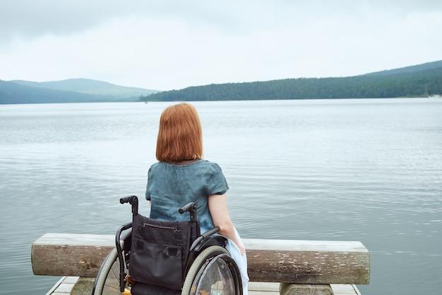 Vista posteriore della donna in sedia a rotelle godendo di una splendida vista sulla natura.